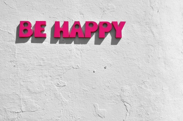 """Foto de uma placa escrita """"be happy"""" (seja feliz) representando as dicas para como motivar funcionários"""