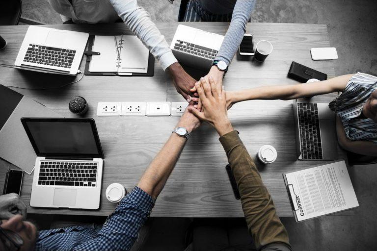 Foto de pessoas com as mãos juntas, representando a ética no trabalho