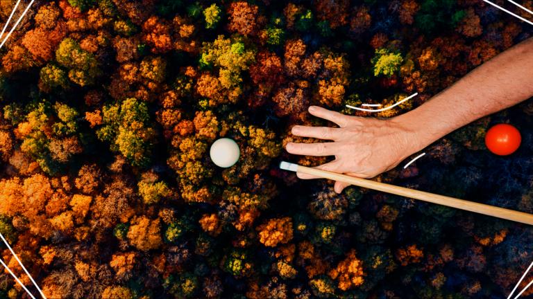 imagem de capa blog com a representação de uma mão jogando sinuca sendo a mesa um fundo com árvores vistas de cima representando o feedback assertivo