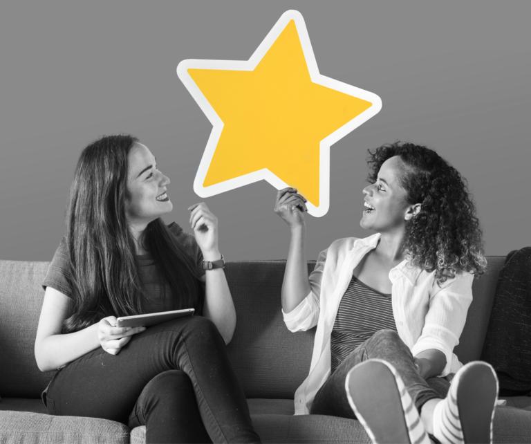 Foto de duas garotas felizes representando a pesquisa de clima organizacional
