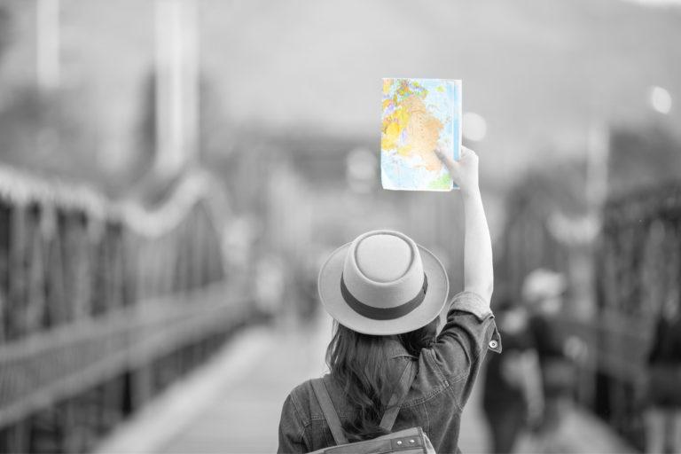 foto de uma mulher viajando com um mapa na mão, representando o dinheiro para viajar
