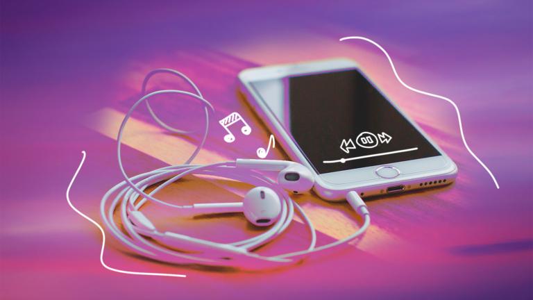 imagem capa blog de um celular com o fone de ouvido em cima de uma mesa representando o podcast
