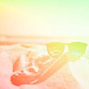 óculos escuro em cima de uma pedra com a praia ao fundo representando as férias de final de ano