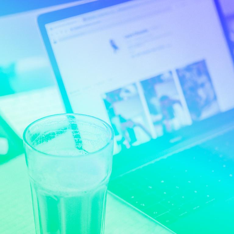 notebook aberto em cima de uma mesa de escritório com um copo de café ao lado esquerdo representando o teletrabalho