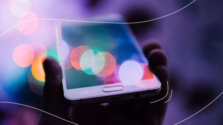 uma mão esquerda segurando um celular com tela virada para cima representando o banco digital