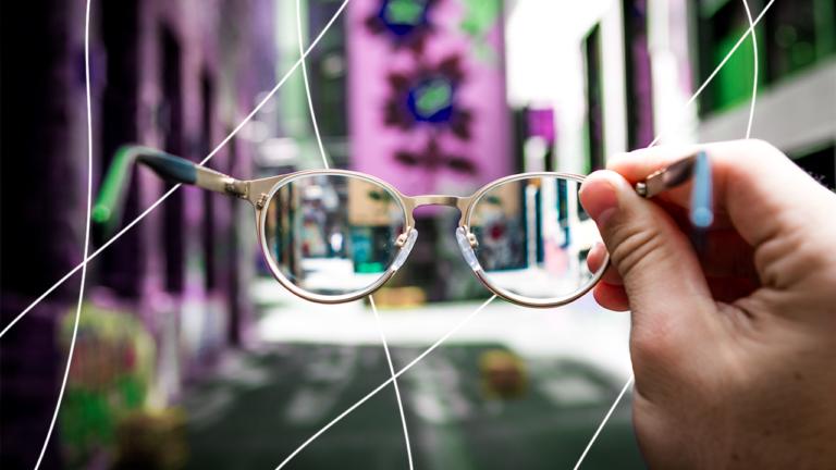 mão esquerda segurando um óculos de grau redondo na frente de uma paisagem com prédios em uma rua urbana, representando a empatia dos colaboradores