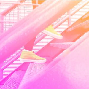 uma escada vista na lateral com pés subindo as escadas representando o papel do rh na saúde física de seus colaboradores