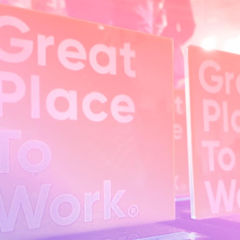 um banner grande em cima de um palco com a logo do Great Place To Work neste banner representando a GPTW