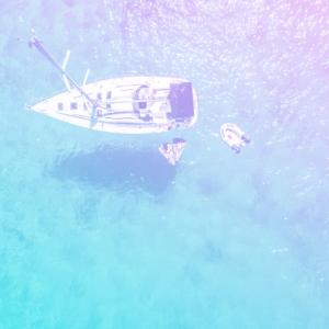 um barco no mar, visto de cima com duas pessoas nadando no mar ao lado do barco representando o onboarding dos sonhos