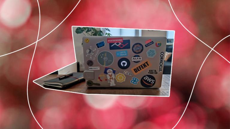 imagem recortada de um notebook sobre uma mesa com a tampa do seu notebook aberta e mostrando vários adesivos de empresas e adesivos que representando o engajamento do colaborador representando a experiência do colaborador na empresa
