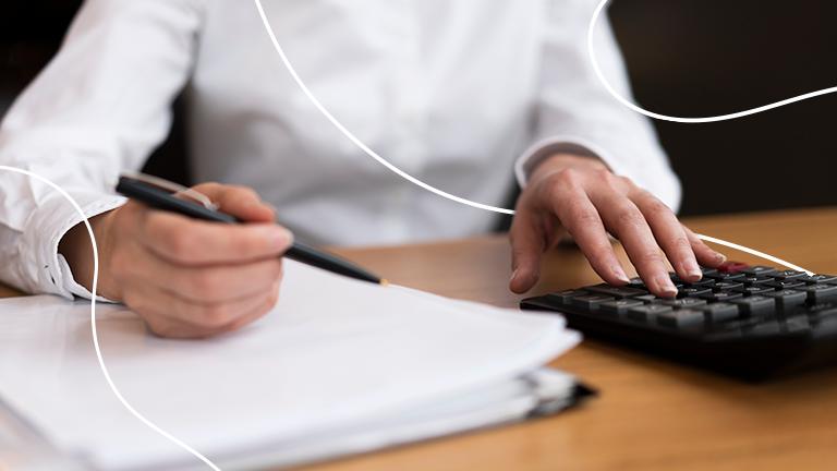 uma pessoa sentada na frente de uma mesa com os braços sobre a mesa segurando uma caneta sobre um caderno e com a oura mão sobre uma calculadora representando as práticas para renegociar dívidas