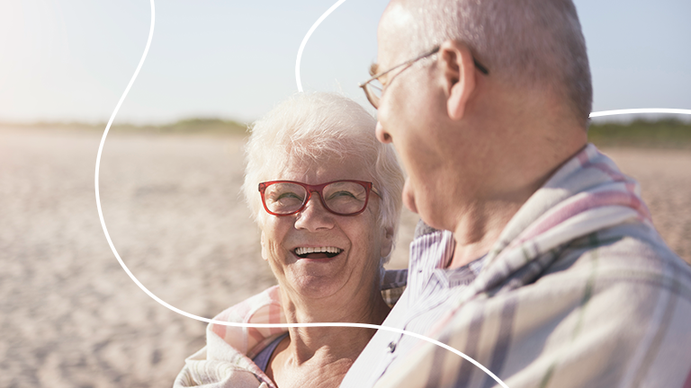 dois idosos se olhando e sorrindo representando como se planejar financeiramente para a terceira idade