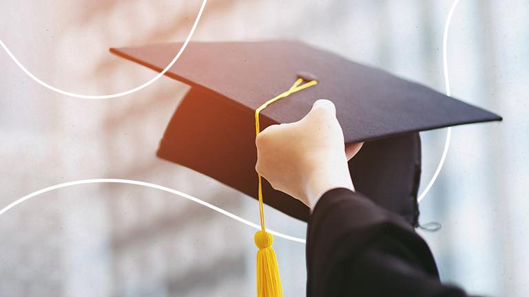 uma mão segurando um chapéu de formatura representando a universidade corporativa