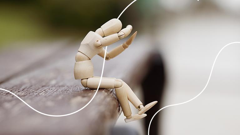 um boneco feito de madeira e todo articulado, sentado sobre uma cadeira com as mãos sobre a cabeça representando o estresse sobre as finanças