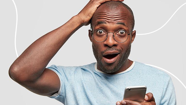 homem com a mão direita na cabeça e com a outra mão segurando o celular com uma expressão assustada, representando os erros que podem levar às dívidas