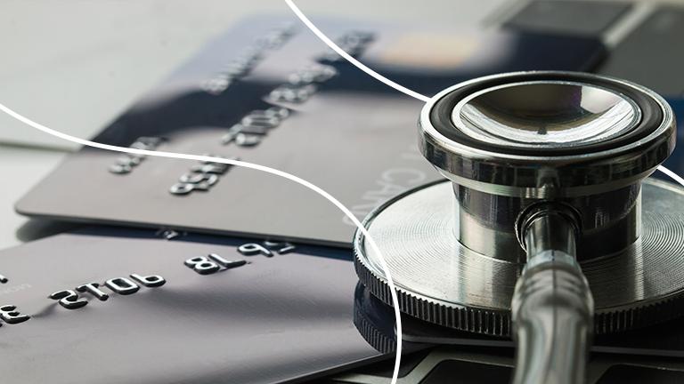 Cartão de crédito e um estetoscópio em cima de uma mesa representando a análise do score de crédito