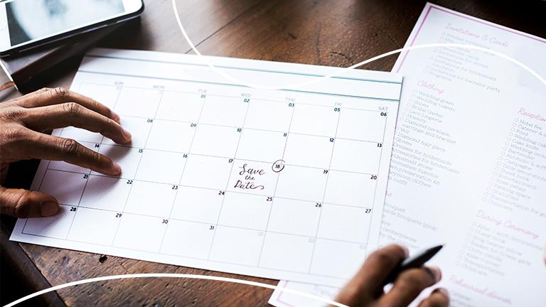 mãos de um homem segurando um calendário com uma data marcada representando o ponto facultativo