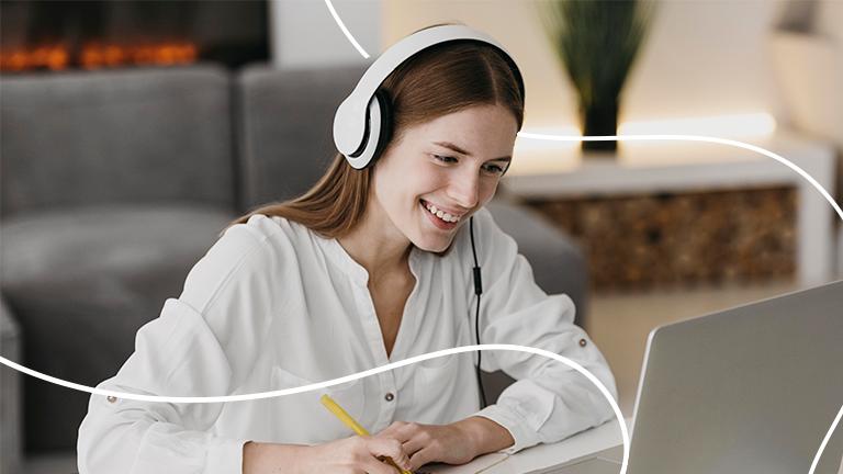 uma mulher sentada numa cadeira e sobre uma mesa com headfones no ouvido, sorrindo e escrevendo algo num papel olhando para tela de seu notebook representando como montar um feedback