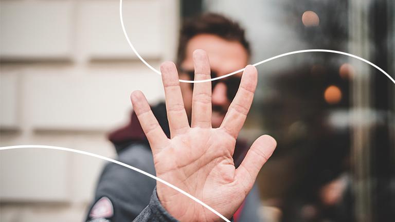 Homem com uma palma da mão levantada, representando a metodologia dos 5s