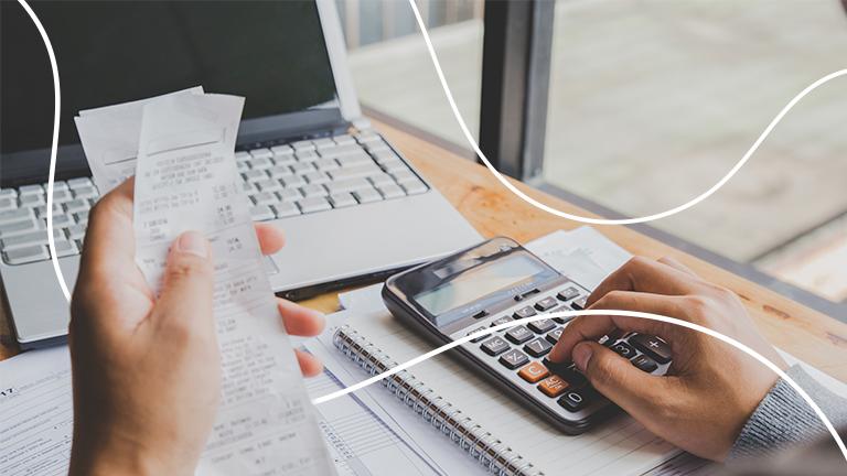 Mesa com computador, papéis e calculadora representando uma pessoa afogada em dívidas