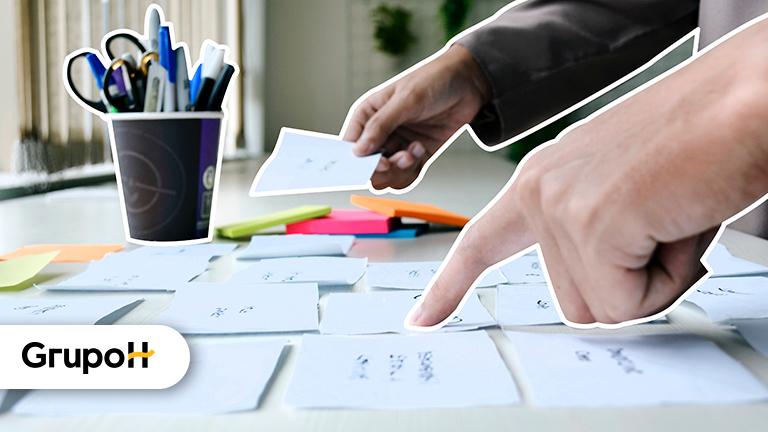 Duas mãos apontando para post-its em uma mesa representando a seleção de currículos para processos de recrutamento e seleção