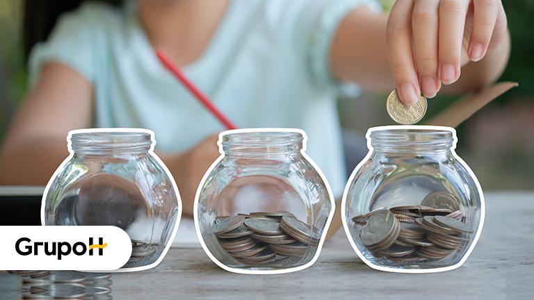 Pessoa em frente a três potes transparentes, cada um com um pouco de moeda, para representar a educação financeira das crianças